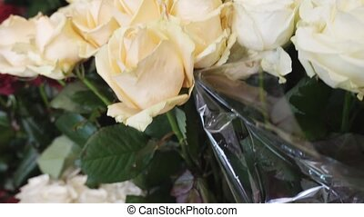 White roses with fragile petals and thorny stems looking...