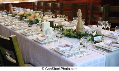 White roses with greenery stand on the festive served dinner...