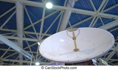 White rotating satellite dish antenna, VSAT parabolic receiver using to receive or transmit information at telecommunication exhibition - slow motion, low angle. Broadcasting, technology concept