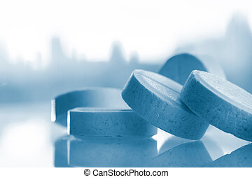 White round pills with blue tint. Medicines on a glass surface against the background of the city.
