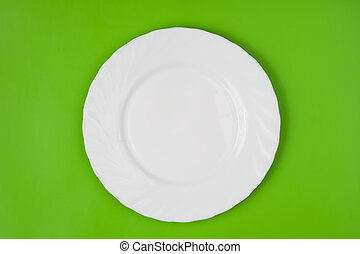 White round plate on green background