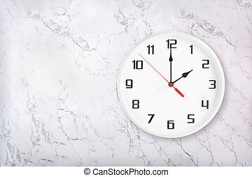 White round wall clock on marble background