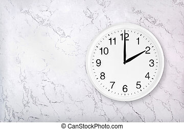 White round wall clock on white natural marble background. Two o'clock.