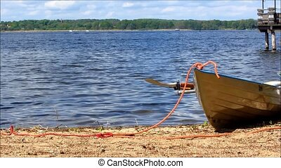 White rowboat on the beach, moored with orange rope.