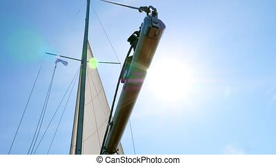 White sail and mast in the sun and glare in summer.