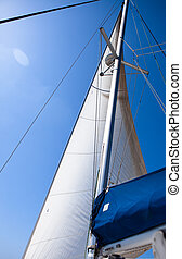 White sail in  sailboat over blue clear sky