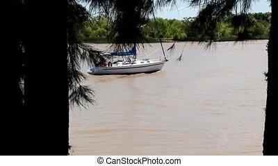 White sailboat navigates the river