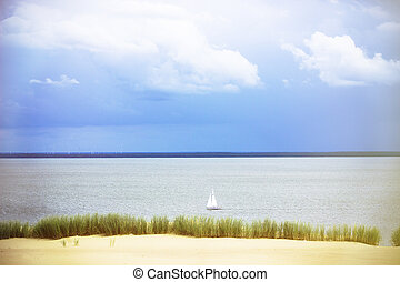 White Sailboat On The Background Of Dunes And Blue Sky