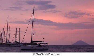White sailing boats anchored in Mediterranean sea against Lipari Islands and colorful sky. Sicily, Italy