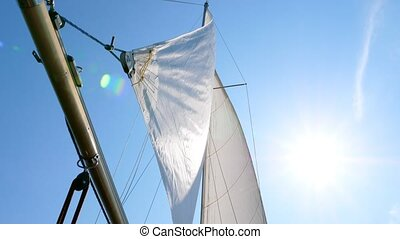 White sails against the blue sky and the sun.