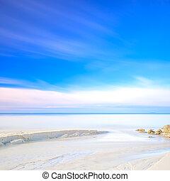 White sand dunes beach, rocks, ocean and sky