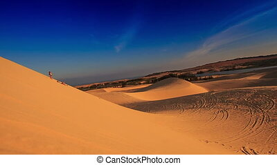 panorama of white sand dunes with tracks distant people jeeps quads motion against blue sky