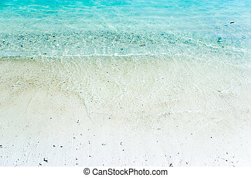 white sand with blue green waves on the beach