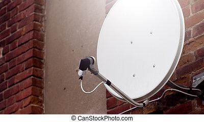White satellite dish on the brick background