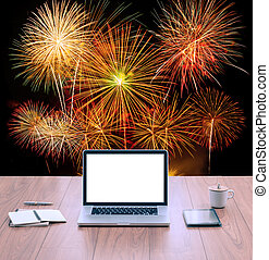 White screen laptop computer on office table with fireworks background