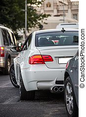 White sedan driving on the central road, waiting in the traffic lights, view from behind