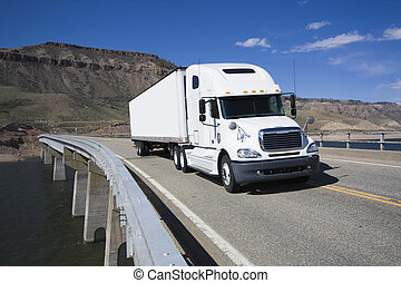 White Semi driving the bridge in Colorado.