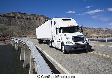 White Semi driving the bridge in Colorado.