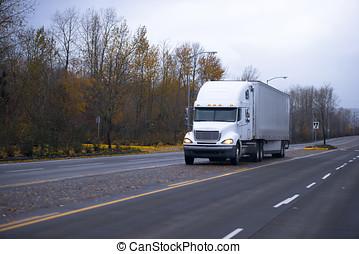 White semi truck and trailer on autumn road - White...