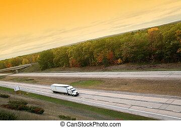 White semi truck cruising on free way