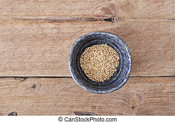 white sesame in cup on wooden