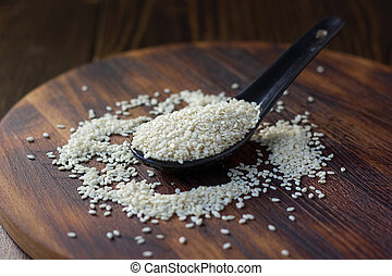 White sesame seeds in a black spoon over wooden background