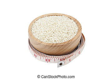 white sesame seeds in wooden bowl with measuring tape ...