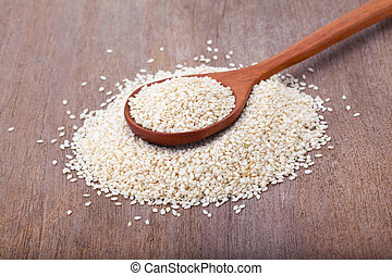 white sesame seeds in wooden spoon on wood background