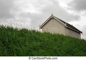 White shed on top of dike