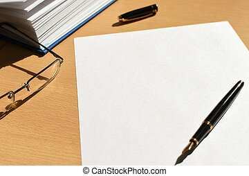 White sheet of paper on a wooden desktop in the office, pen, accessories, glasses, copy space