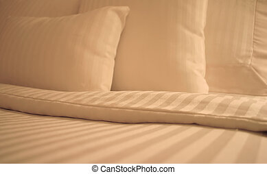 Detail of bed with set of crisp striped sheets and pillows