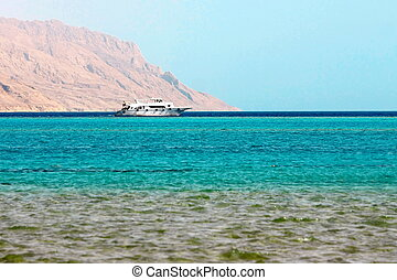 White ship in blue sea on mountain background in Red Sea