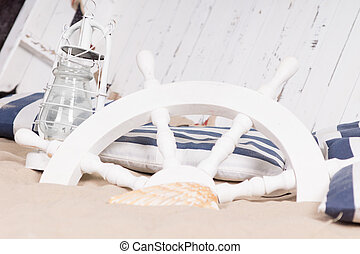 White ships wheel buried in sand with a hurricane lamp and...