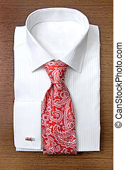 white shirt with red tie on wooden shelf