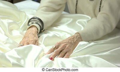 White silk and old woman manicured hands. Senior woman hands...