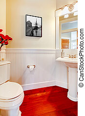 White small elegant bathroom with red wood floor.