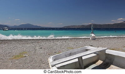 White small rowboat boat dry docked on the beach - Small...