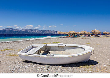 White small rowboat boat dry docked on the beach