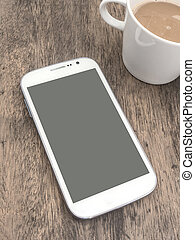 White smart phone and cup of coffee