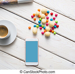 White smart phone on a desktop. Clipping path included.