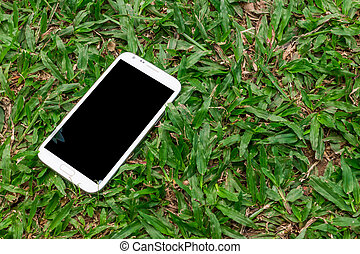 White smart phone with blank screen on green grass