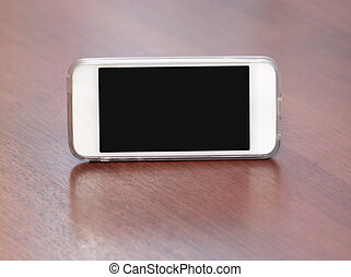 White smart phone with isolated screen on wooden desk