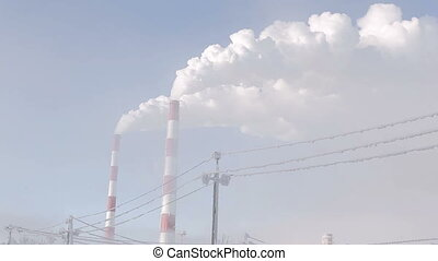 White smoke from industrial chimney on a light background of blue sky.