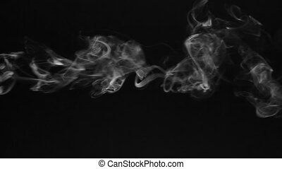 White smoke in the form of rings on a black background.
