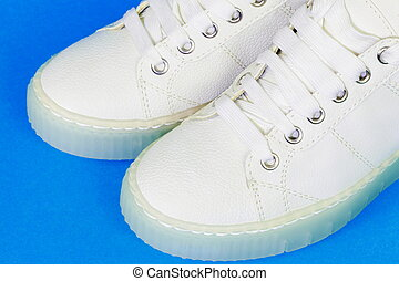White sneakers on blue close up