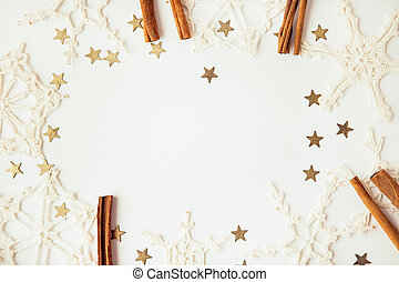 White snowflakes, gold stars and cinnamon sticks on the white background, copy space for text