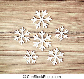 White snowflakes on the wooden background, symbol of winter