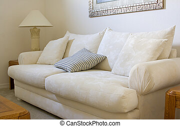 A white sofa with cushions in a living room of a residential home