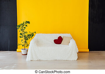 white sofa in the interior of the room with a yellow background