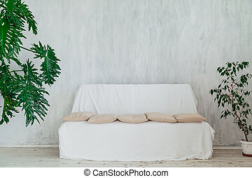 white sofa with plants in the interior of the gray room of the house